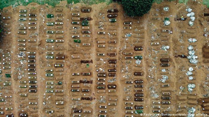 Foto aérea mostra um grande número de covas improvisadas, com os caixões à mostra.