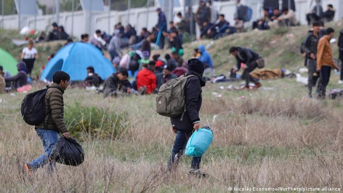 Mit Rucksäcken bepackte Menschen zwischen Zelten vor einer Mauer