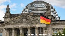 im 30. Jahr der deutschen Einheit weht die Bundesflagge weht vor dem Portal des Reichstagsgebäude in Berlin mit dem Schriftzug: Dem Deutschen Volke. Der Reichstag am Platz der Republik ist seit 1999 Sitz des Deutschen Bundestages. Foto: Winfried Rothermel