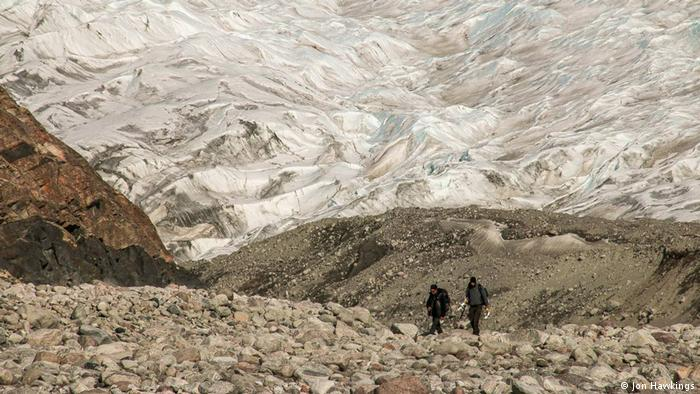 Two researchers hiking up a mountain in Greenland