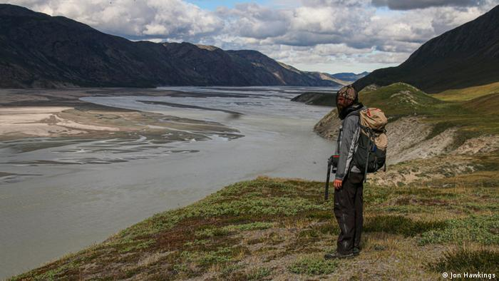 A researcher standing by a river in Greenland
