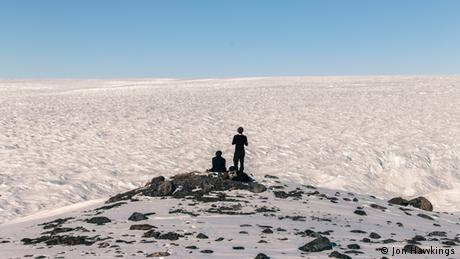 Two people looking out over Greenland's icy landscape from a hill