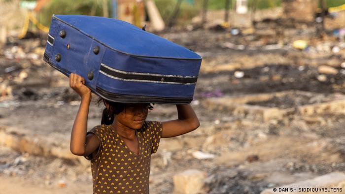 ARohingyarefugee carries her belongings to a temporary shelterafter afiredestroyed a Rohingya refugee camp