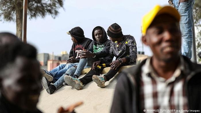 African migrant day labourers seeking small jobs, wait under a bridge in the Libyan capital Tripoli to be hired by potential employers