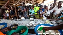 """*** Dieses Bild ist fertig zugeschnitten als Social Media Snack (für Facebook, Twitter, Instagram) im Tableau zu finden: Fach """"Images"""" *** KYANGWALI, UGANDA - APRIL 10: Refugees from the Democratic Republic of Congo are given a lunch consisting of maize and peas from the World Food Programme by volunteers in the Kagoma reception centre within the Kyangwali settlement on April 10, 2018 in Kyangwali, Uganda. According to the UNHCR around 70,000 people have arrived in Uganda from the Democratic Republic of Congo since the beginning of 2018 as they escape violence in the Ituri province. The majority of refugees are arriving by boat across Lake Albert, which lies between the two countries. With refugee settlements in Uganda almost at maximum capacity there are plans for new settlements to be built to deal with the continuing influx of people. A cholera outbreak in the settlements has left at least 42 dead and many hundreds severely affected. The World Food Programme anticipates providing food and nutrition for up to 1.6 million refugees this year. Fighting in DRC between the Hema and Lendu communities has seen villages being burnt and dozens killed in the fresh outbreak of violence. (Photo by Jack Taylor/Getty Images)"""