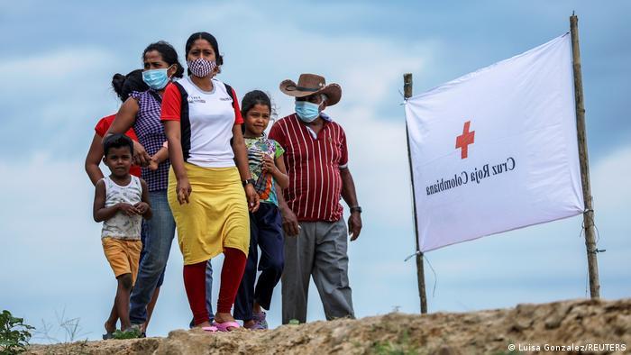 Família de refugiados venezuelanos próxima a uma faixa da Cruz Vermelha na Colômbia