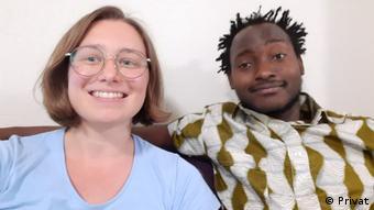 Uma garota branca de óculos e blusa azul sentada ao lado de um jovem negro sorrindo