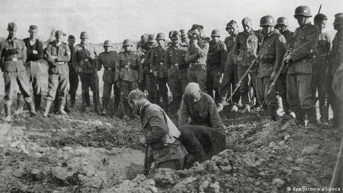Німецькі солдати примушують радянських полонених солдатів рити собі могили