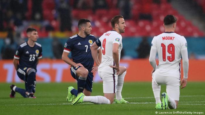 Jogadores ajoelhados em campo, em protesto contra o racismo