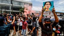 A protester holds up a painting of Myanmar's detained civilian leader Aung San Suu Kyi to mark her birthday during a demonstration against the military coup in Yangon on June 19, 2021. (Photo by STR / AFP)