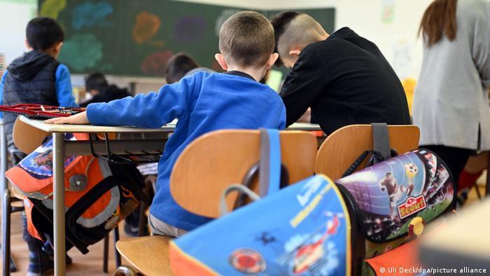 Children sit at school desks in a classroom