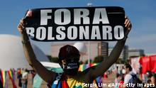 An activist holds a sign during a protest by opposition parties and social movements against Brazilian President Jair Bolsonaro's handling of the COVID-19 pandemic in Brasilia, on June 19, 2021. - Far-right President Jair Bolsonaro has been facing criticism for his management of the pandemic, including initially refusing offers of vaccines, as epidemiologists warn Brazil may now be on the brink of a third wave of Covid-19. (Photo by Sergio Lima / AFP) (Photo by SERGIO LIMA/AFP via Getty Images)