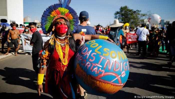 A protester holds a ball criticizing Brazilian President Jair Bolsonaro's coronavirus response at a protest in Brasilia