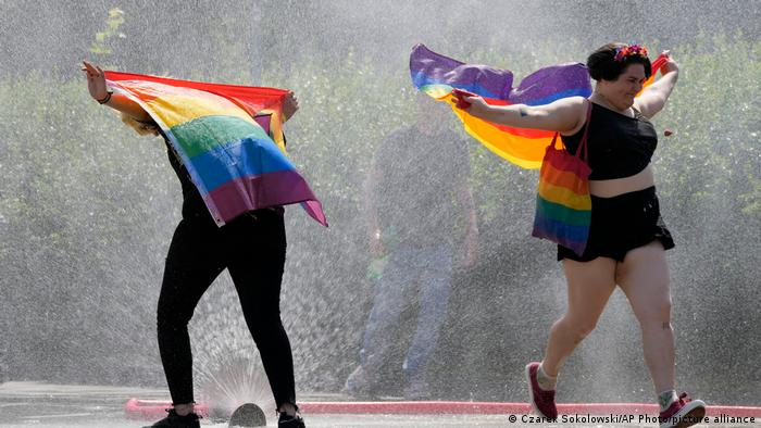 Two people with rainbow flags run through a fountain in Warsaw, Poland