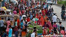 People shop at a crowded roadside vegetable market after authorities eased coronavirus restrictions, following a drop in COVID-19 cases in Ahmedabad, India, June 15, 2021. REUTERS/Amit Dave