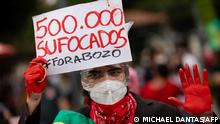 Manifestante de máscara levanta papel com inscrição 500.000 sufocados, fora Bozo