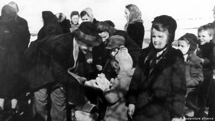 A black and white photo showing Polish refugees arriving in Germany