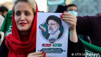 Жительница Тегерана держит в руках плакат с изображением Раиси, 19 июня 2021 года