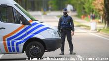 A Belgian police officer stands at a road block during a manhunt for a fugitive soldier
