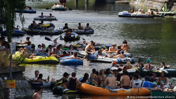 Dozens of people sit on rubber boats in a canal in Berlin as part of a protest against coronavirus restrictions