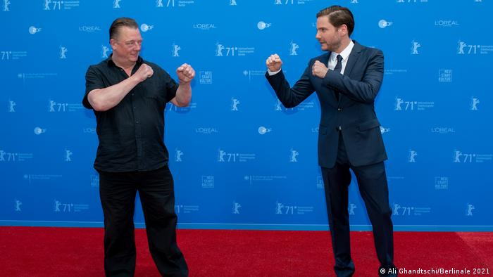 Peter Kurth and Daniel Brühl on stage holding up fists like boxers at the Berlinale 2021.