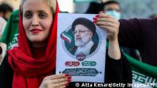 TOPSHOT - A woman holds a picture of Iran's newly-elected president Ebrahim Raisi as supporters celebrate his victory in Imam Hussein square in the capital Tehran on June 19, 2021. (Photo by ATTA KENARE / AFP) (Photo by ATTA KENARE/AFP via Getty Images)