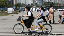 Women wearing face masks as a precaution against the coronavirus ride a bicycle at a public park along the Han River in Seoul, South Korea, Sunday, May 9, 2021. (AP Photo/Ahn Young-joon)