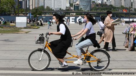 Women wearing face masks ride a bicycle in South Korea