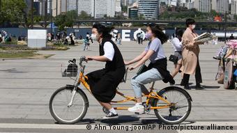 Прохожие и велосипедисты в защитных масках на улицах Сеула