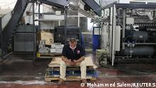 A Palestinian worker uses a mobile phone at Gaza Pepsi factory for soft drinks in Gaza City June 21, 2021. REUTERS/Mohammed Salem