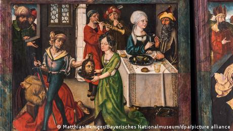 A painting with a medieval portrayal of different scenes, including a depiction of an executioner handing Princess Salome the severed head of St. John the Baptist.