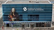 The logo of the airport reading the new name of the Nuremberg airport 'Albrecht Duerer Airport Nuernberg' is attached to a building of the airport in Nuremberg, Germany, 11 June 2015. Next to the logo the image 'Selbstbildnis im Pelzrock'(Self portrait in fur coat) by Albrecht Duerer can be seen. Photo:DANIELKARMANN/dpa