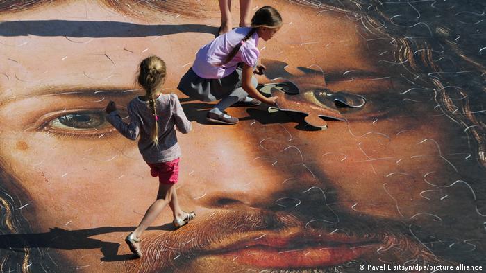 Kinder im russischen Yakaterinburg ergänzen das letzte Teil eines überdimensionalen Puzzle von Dürers Selbstbildnis mit Pelzmantel zusammen.