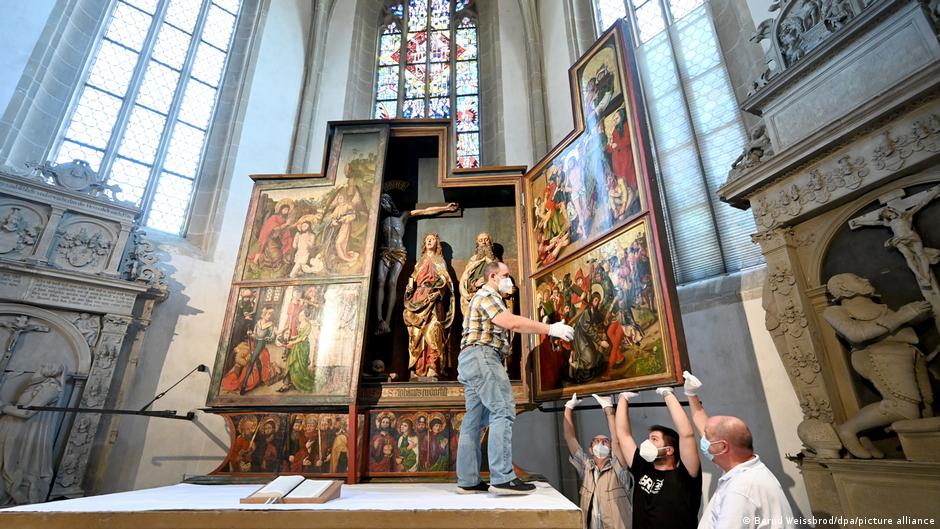 Men holding up panel of the altar, with perhaps new artwork by Albrecht Dürer.