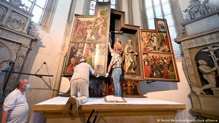 Zwei Männer klappen den Seitenflügel des Altars zu, so dass man das Gemälde an seiner Außenseite sehen kann.