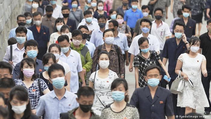 Foto mostra muitas pessoas andando em uma rua. Todas usam máscara.