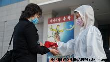 An audience member undergoes a health check as part of preventative measures against the Covid-19 coronavirus, before a performance by the North Korea's National Acrobatic Troupe at the Pyongyang Circus Theater as part of celebrations marking the annual Mother's Day public holiday, in Pyongyang on November 16, 2020. (Photo by KIM Won Jin / AFP) (Photo by KIM WON JIN/AFP via Getty Images)