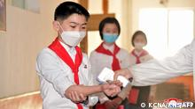 This undated picture released from North Korea's official Korean Central News Agency (KCNA) on May 16, 2021 shows students having their temperature checked as a preventive measure against the COVID-19 coronavirus at a school in Pyongyang. (Photo by STR / KCNA VIA KNS / AFP) / South Korea OUT / ---EDITORS NOTE--- RESTRICTED TO EDITORIAL USE - MANDATORY CREDIT AFP PHOTO/KCNA VIA KNS - NO MARKETING NO ADVERTISING CAMPAIGNS - DISTRIBUTED AS A SERVICE TO CLIENTS / THIS PICTURE WAS MADE AVAILABLE BY A THIRD PARTY. AFP CAN NOT INDEPENDENTLY VERIFY THE AUTHENTICITY, LOCATION, DATE AND CONTENT OF THIS IMAGE --- /