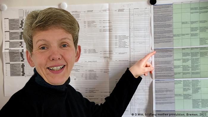 Eine Frau mit kurzen blonden Haaren im schwarzen Rolli lächelt in die Kamera und deutet mir ihrem linken Zeigefinger auf eine Wand hinter ihr mit eng bedruckten Tabellen