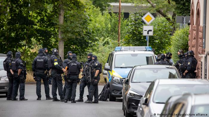 A group of armed German police stand near a police van and other cars in the road