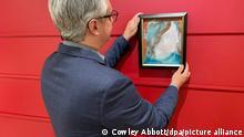 17.06.2021 *** Rob Cowley, Präsident & Senior Spezialist bei Cowley Abbott, hängt ein zufällig in einem Spendenzentrum für Haushaltsgegenstände entdecktes Gemälde von Musik-Legende David Bowie (1947-2016) an die Wand. Das Gemälde wird nun in Kanada versteigert. (zu dpa: «In Spendenzentrum entdecktes Bowie-Gemälde wird in Kanada versteigert») +++ dpa-Bildfunk +++