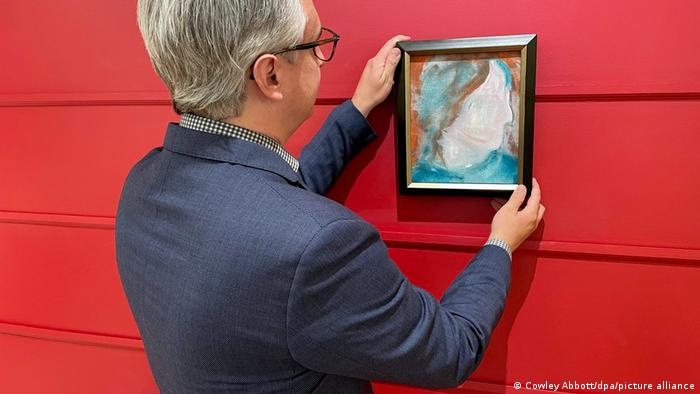 A man hanging a painting by David Bowie on a red wall.