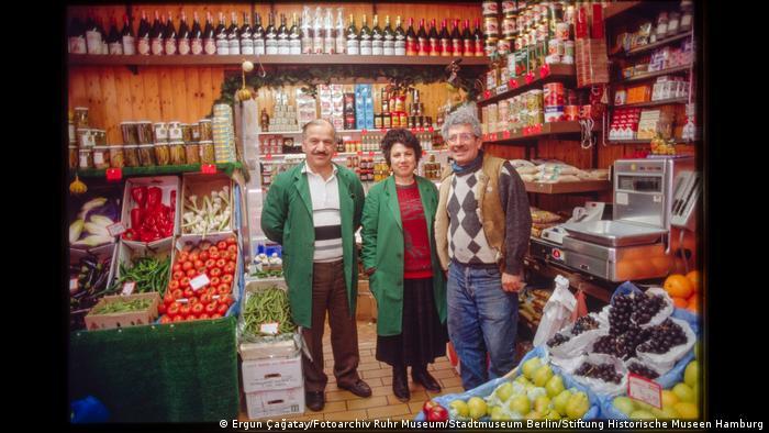 Drei Menschen stehen in einem Lebensmittelladen und lächeln in die Kamera. Foto aus der Ausstellung Wir sind von hier. Deutsch-Türkisches Leben 1990