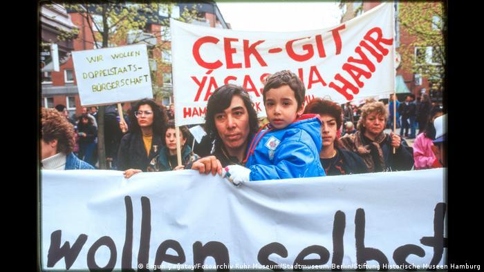 Demonstrierende mit Bannern. Foto aus der Ausstellung Wir sind von hier. Deutsch-Türkisches Leben 1990