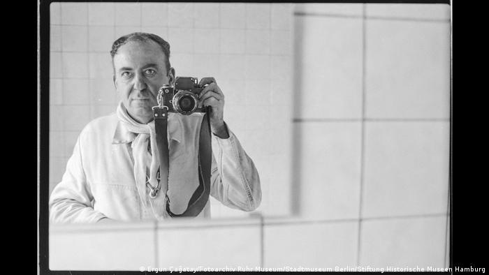 Der Fotograf Fotograf Ergun Çağatay fotografiert sich in einem Spiegel mit einer Spiegelreflex-Kamera. Aus der Ausstellung Wir sind von hier. Deutsch-Türkisches Leben 1990