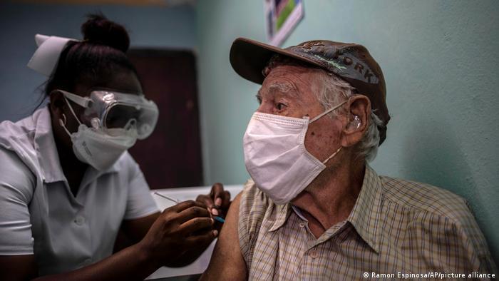 A nurse inoculates an elderly man