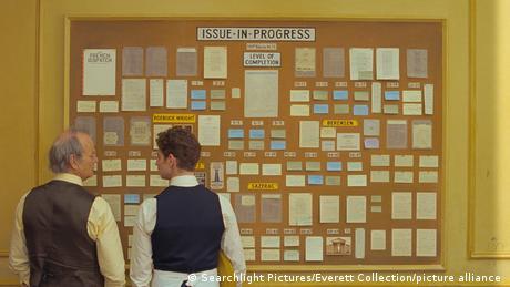 Filmstill von 'The French Dispatch' mit Bill Murray und Pablo Pauly vor einem Themenboard 'Issue-in-progress'