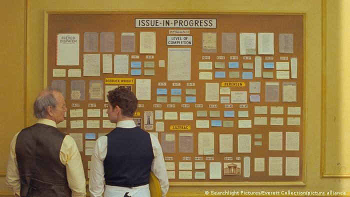 Film still 'The French Dispatch' Bill Murray and Pablo Pauly stand in front of an 'Issue-in-progress' pinboard
