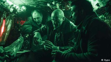 Filmstill aus 'Petrov's Flu': drei Männer in einem grün beleuchteten Raum.