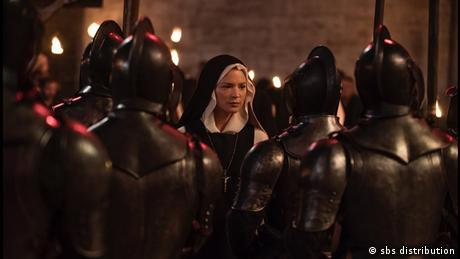 Filmstill von 'Benedetta': Nonne umringt von Soldaten in voller Eisenmontur.